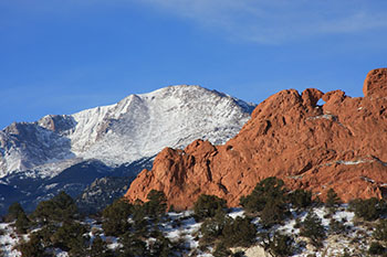 The red rocks of Garden of the Gods with Pikes Peak behind them.