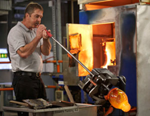 A worker blows molten crystal into a vase at House of Waterford.