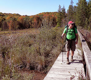 A hiker crossing the old boardwalk along the Jordan River Pathway.